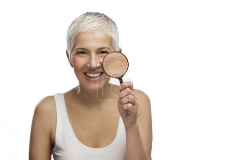 Portrait of a beautiful elderly woman holding a magnifying glass, isolated on white background