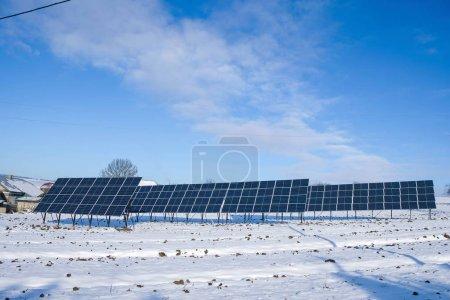 Photo pour Rangée de panneaux solaires le matin ensoleillé d'hiver sur un champ enneigé dans un village ukrainien. Table des matières. - image libre de droit