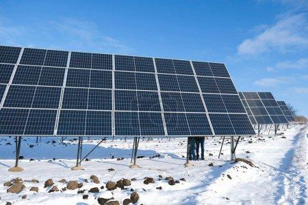 Photo pour Une série de panneaux solaires le matin ensoleillé d'hiver sur un champ de neige en Ukraine. Fragment de deux jambes d'homme sur un panneau solaire. - image libre de droit