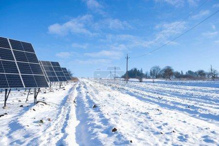 Photo pour Fragments de panneaux solaires le matin ensoleillé d'hiver sur un champ de neige en Ukraine. Le concept d'énergie verte en milieu rural. - image libre de droit