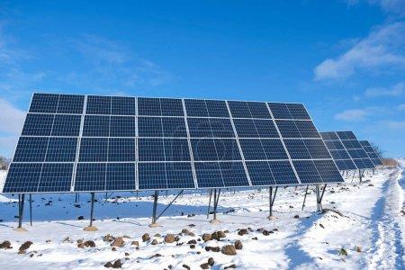 Photo pour Panneaux solaires le matin ensoleillé d'hiver sur un champ enneigé en Ukraine. Le concept d'énergie verte en milieu rural. - image libre de droit