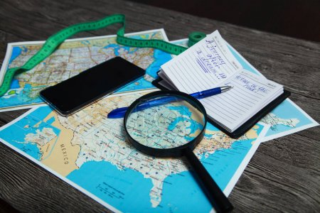 On the table is a map of the United States, phone, meter, pen, magnifier and notebook. People are planning to travel.
