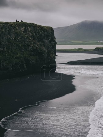 tourists standing on cliff and looking at black sand beach, Vik, Iceland