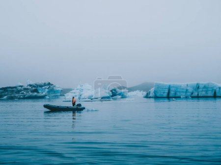 boat with person in melting glacier lagoon Jokulsarlon in Iceland