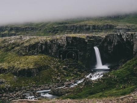 Photo pour Belle vue sur la falaise avec cascade lors d'une journée brumeuse en Islande - image libre de droit