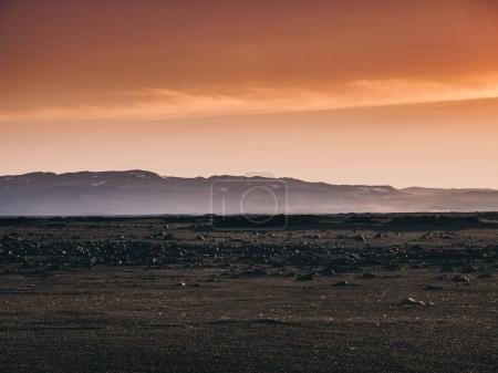 Photo for Scenery with black sand, rocks and mountains at sunset, Iceland - Royalty Free Image