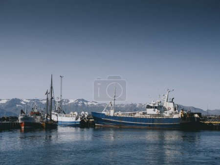 Fishing boats and snowy mountains in Husavik harbour, Iceland