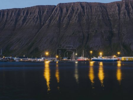 Photo for Fishing boats and dark cliff at night in Husavik harbour, Iceland - Royalty Free Image