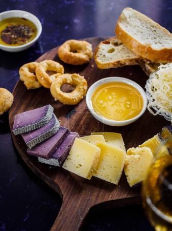 Photo pour Vue rapprochée de fromages variés, sauce et pain sur planche à découper en bois - image libre de droit