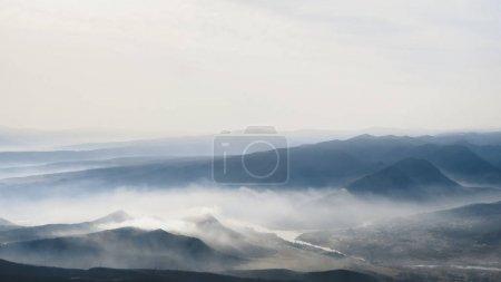 Photo pour Vue panoramique sur les montagnes dans le brouillard et le ciel - image libre de droit