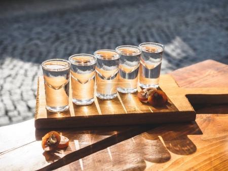 Photo pour Vue rapprochée des verres avec chacha et délicieuse churchkhela traditionnelle tranchée sur table en bois - image libre de droit