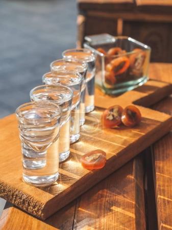 Photo pour Foyer sélectif de verres avec chacha et délicieuse traditionnelle tranches de churchkhela sur table en bois - image libre de droit