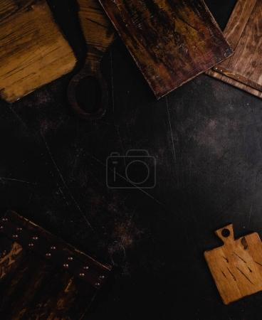 top view of wooden cutting boards on black concrete surface