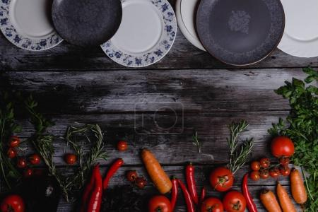 Photo for Top view of raw vegetables with plates on wooden table - Royalty Free Image