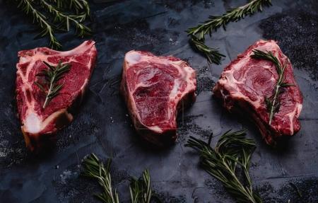Photo pour Gros plan de viande crue avec romarin sur une surface en béton noir - image libre de droit
