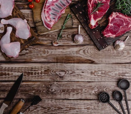 top view of various raw meat and kitchen utensils on wooden table