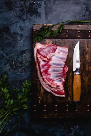 Photo for Top view of raw beef ribs on wooden board with knife on dark concrete surface - Royalty Free Image