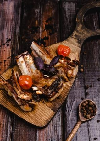 Photo for Close-up shot of delicious grilled ribs on wooden cutting board - Royalty Free Image