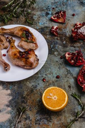 delicious grilled chicken legs with pomegranade seeds and orange on concrete surface