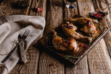 close-up shot of delicious grilled chicken legs on wooden board with cutlery