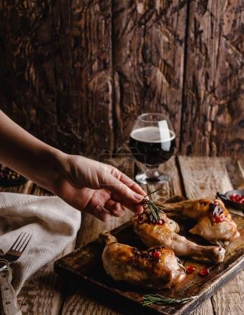 Photo pour Plan recadré de femme ajoutant du romarin à de délicieuses viandes grillées - image libre de droit