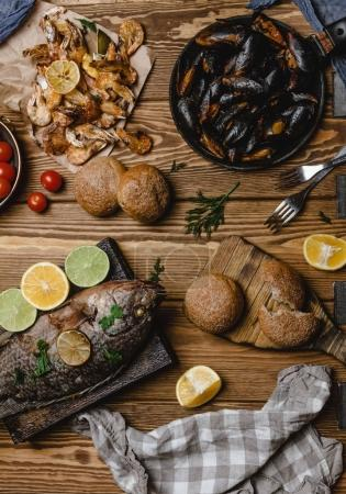 Top view of assorted seafood and baked fish with bread and tomatoes on wooden table