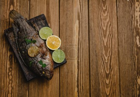 Photo for Top view baked fish with lemon and herbs on wooden board - Royalty Free Image