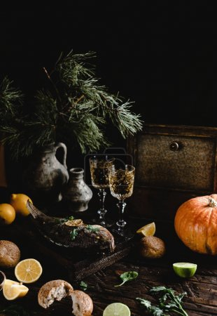 Baked fish with lemon and herbs on wooden board with white wine glasses on dark wooden table