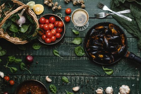 Top view of cooked mussels with shells served in pan with tomatoes, herbs and wine on rustic table