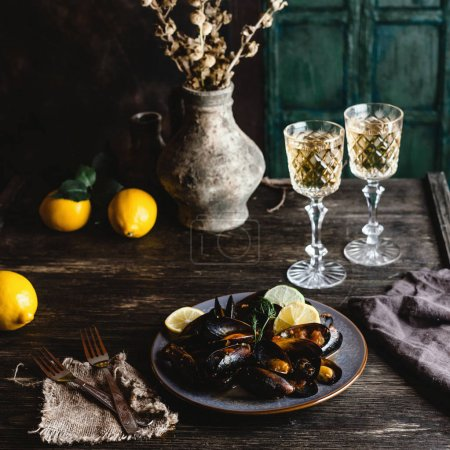Photo for Cooked mussels with shells served on plate with two glasses of white wine on wooden table - Royalty Free Image