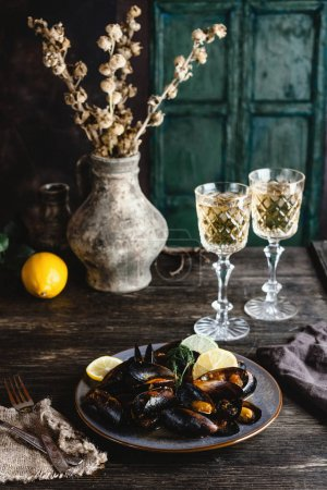 Cooked mussels with shells served on plate with two glasses of white wine on wooden table