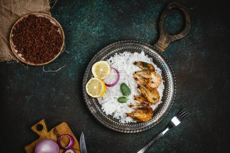 Top view of cooked shrimps with lemon and onion on rustic metal tray with rice side dish on dark table