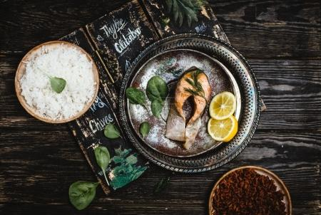 Top view of baked salmon steak with lemon on rustic metal tray with rice side dish on dark wooden table