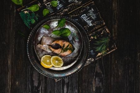 Photo pour Vue de dessus de délicieux cuit le poisson avec des herbes et tranches de citron sur la table en bois rustique - image libre de droit
