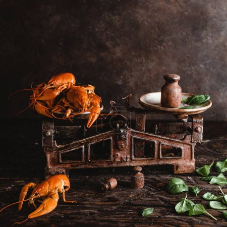 Photo for Close-up view of gourmet lobsters on vintage scales and basil leaves on rustic wooden table - Royalty Free Image