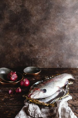 close-up view of fresh raw fish on vintage plate and onions on rustic table