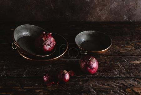 close-up view of old fashioned utensils with red onions on rustic wooden table