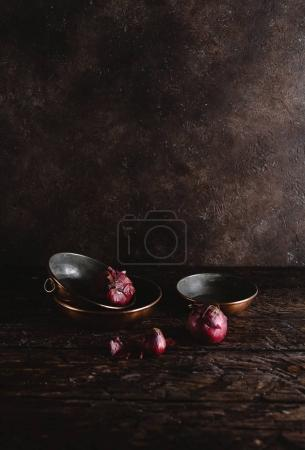 close-up view of vintage utensils with red onions on rustic wooden table