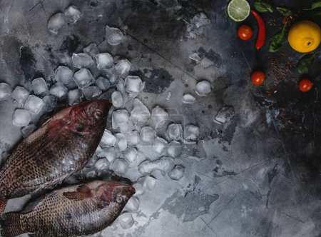 top view of fresh raw sea fish on ice cubes with lime, lemon, spices and cherry tomatoes on grey