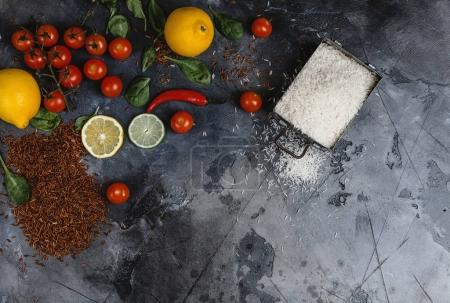 top view of raw rice in container, spices and vegetables on scratched grey surface
