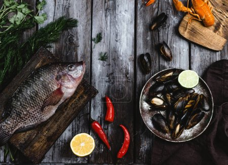 Photo for Top view of raw fish on cutting board and mussels with lime on rustic wooden table - Royalty Free Image