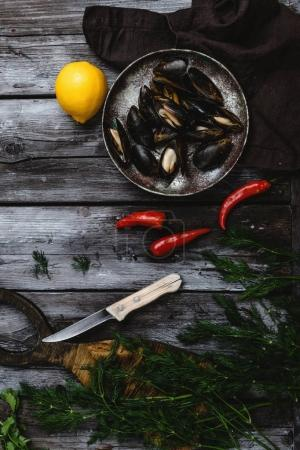 top view of delicious mussels with shells on vintage plate with herbs, chili peppers and lemon on rustic wooden table