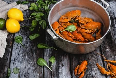 close-up view of delicious lobsters in pan and herbs with citrus fruits on rustic wooden table