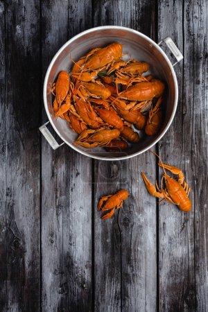top view of gourmet lobsters in pan on rustic wooden table
