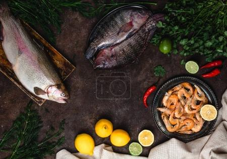 Photo for Top view of fresh fish, chili peppers, shrimp, herbs with lemons and tablecloth on dark table top - Royalty Free Image