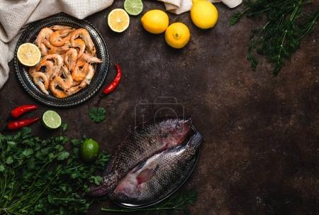 Photo pour Poisson cru, piments, crevettes, herbes aux citrons et nappe sur le dessus de table sombre - image libre de droit