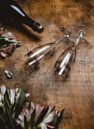 Photo pour Fleurs, bouteille de champagne et verres sur une table en bois - image libre de droit