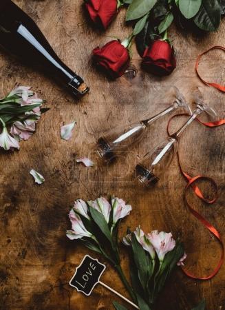 Photo pour Vue de dessus des fleurs, bouteille de champagne, verres et signe d'amour sur la table en bois - image libre de droit