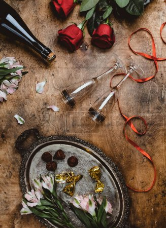 top view of flowers, champagne bottle, glasses and chocolate candies on wooden table, valentines day concept