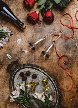 Photo pour Vue de dessus des bonbons de chocolat, bouteille et les verres fleurs, champagne sur table en bois, concept Valentin - image libre de droit